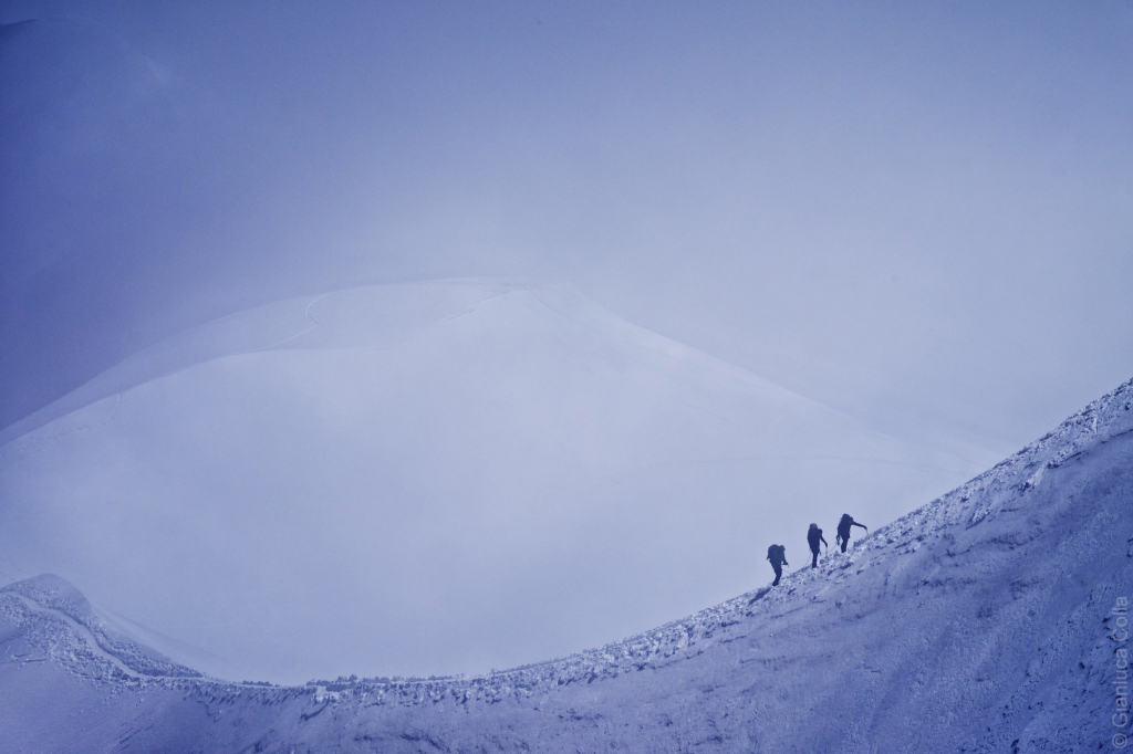 Three climbers on a side of a glacier, climbing the Mount Blanc.